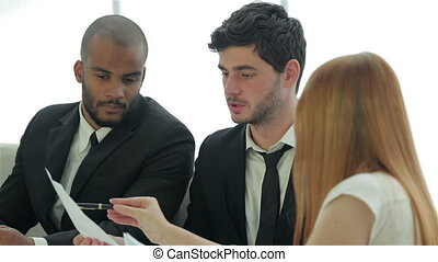 Businessmen sitting at table in office while discussing their business doings