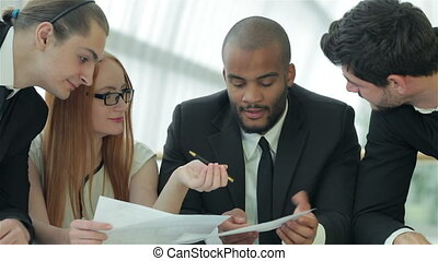 Businessmen sitting at table in office while discussing their of business doings
