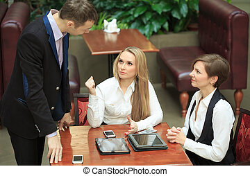 Businessmen sitting in cafe for a laptop. two girls
