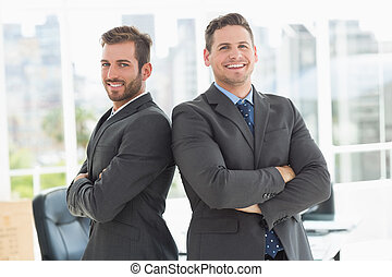 Businessmen standing with arms crossed in office