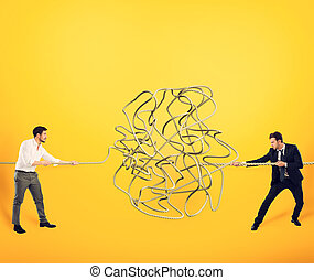 Businessmen try to solve a tangled rope. Concept of partnership