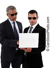 Businessmen wearing sunglasses and looking at a laptop