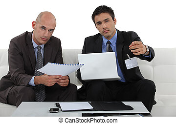Businessmen with a laptop on a sofa