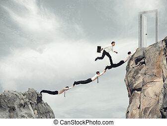 Businessmen working together to reach a door