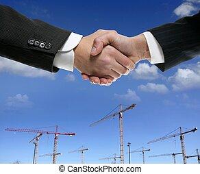 Businessmn handshake in construction crane area over blue sky