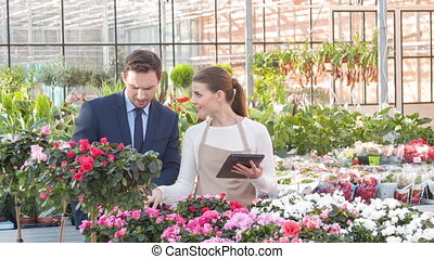 Businesspeople are checking the growing flowers.