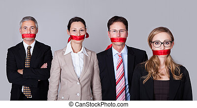 Businesspeople bound by red tape around their mouths ...