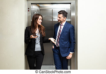 Businesspeople Coming Out From An Elevator