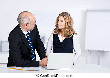 Businesspeople communicating while looking at each other at desk in office