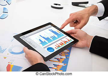 Businesspeople Comparing Graphs On Digital Tablet
