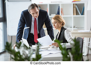 Businesspeople discussing documents