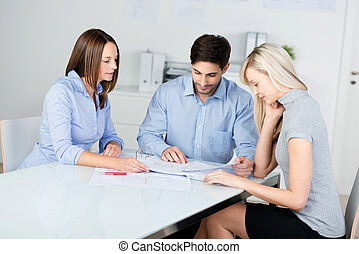 Businesspeople Discussing Over Blueprint At Conference Desk