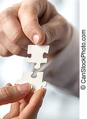 Businesspeople fitting together matching interlocking puzzle pieces