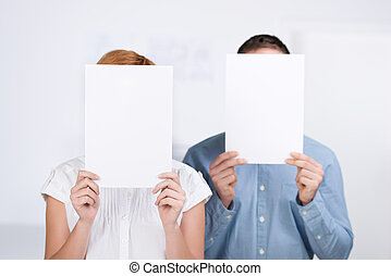 Businesspeople Holding Blank Paper In Front Of Their Faces