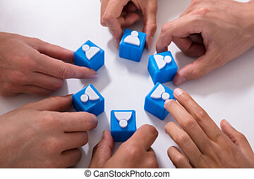 Businesspeople Holding Cubic Blocks With Human Figures