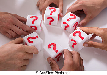 Businesspeople Holding Cubic Blocks With Question Mark Sign