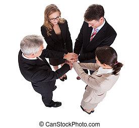 Businesspeople holding hands - teamwork