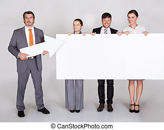Group Of Businesspeople In A Row Holding Placard
