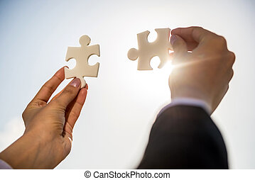 Businesspeople holding puzzle