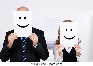 Businesspeople Holding Smileys On Placard In Front Of Faces...