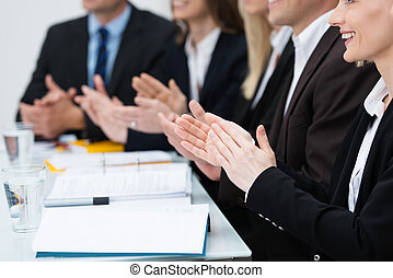 Businesspeople in a meeting applauding