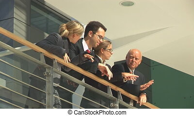 businesspeople in discussion on balcony