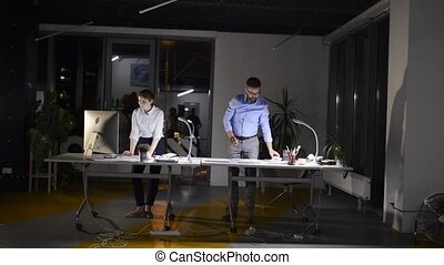 Businesspeople in the office at night working late. - Two...