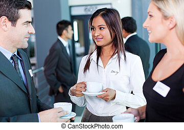 businesspeople interacting during conference coffee break -...