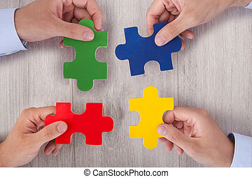Businesspeople Joining Multicolored Puzzle Pieces At Desk -...