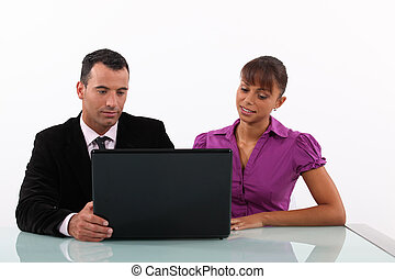 Businesspeople looking at a laptop