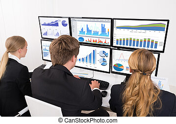 Businesspeople Looking At Financial Graphs On Multiple Computer