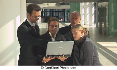 businesspeople looking into laptop