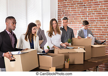 Businesspeople Packing Belongings In Cardboard Box