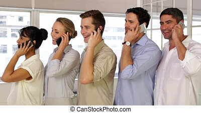 Businesspeople phoning while standing in a row in the office