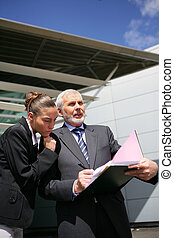 Businesspeople reviewing paperwork outside
