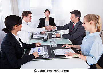 Businesspeople Shaking Hand In Meeting