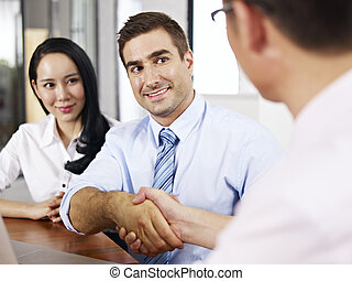 a caucasian businessman shaking hands with his asian partner before meeting.