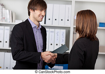 Businesspeople Shaking Hands In Office - Businessman and...