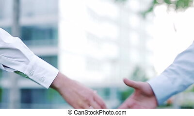 Businesspeople shaking hands outdoors