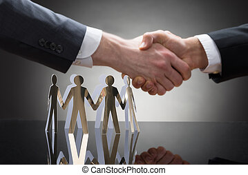 Businesspeople Shaking Hands With Paper Figures
