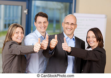 Businesspeople Showing Thumbs Up Sign In Office