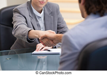 Businesspeople sitting while shaking hands