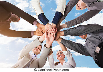 Businesspeople Stacking Their Hands - Low Section View Of...