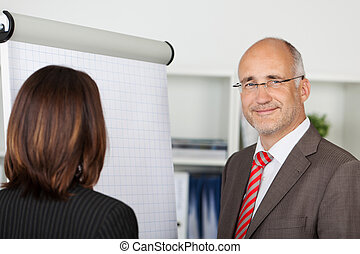 businesspeople standing by flipchart