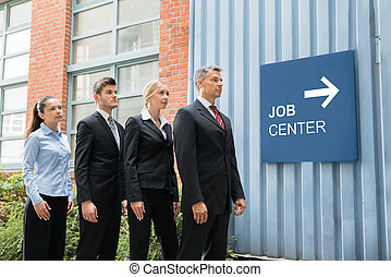 Businesspeople Standing Near The Job Center Signboard