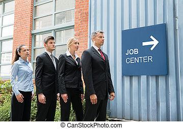 Businesspeople Standing Near The Job Center Signboard -...
