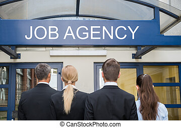 Businesspeople Standing Outside Job Agency - Rear View Of...