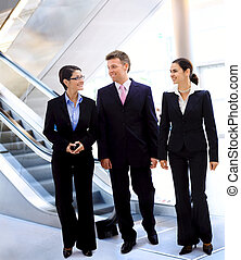 Businesspeople talking - Happy young businesspeople walking...