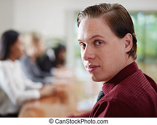 businesspeople talking in meeting room and man smiling