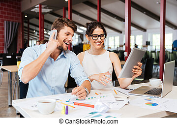 Businesspeople talking on cell phone and using tablet in office